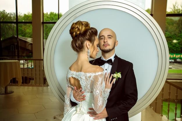 Portrait de beau couple marié étreignant et posant à la caméra