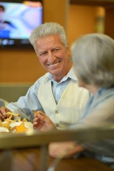 Portrait de beau couple de personnes âgées mangeant de la restauration rapide
