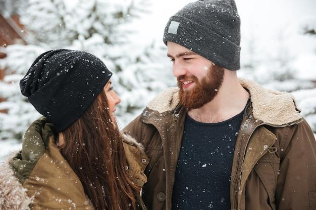 Portrait de beau couple souriant dans la forêt d'hiver