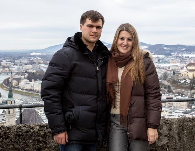 Portrait d'un beau couple souriant posant contre le paysage urbain à une journée froide