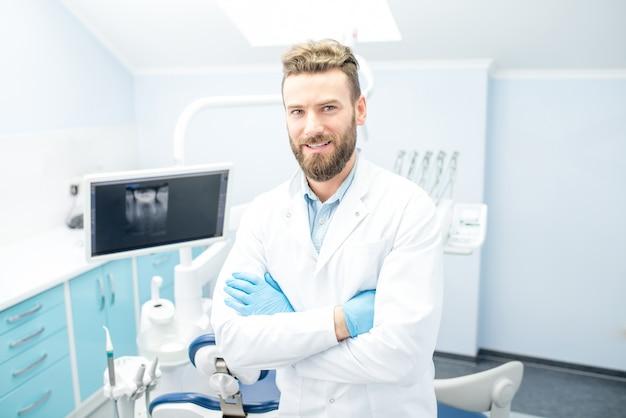 Portrait de beau dentiste en uniforme au cabinet dentaire