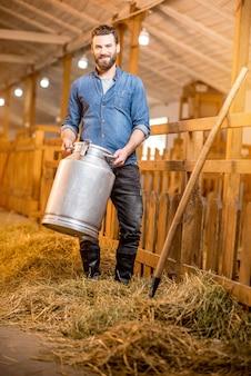 Portrait d'un beau fermier debout avec un récipient à lait rétro à l'étable des chèvres. production de lait naturel et élevage