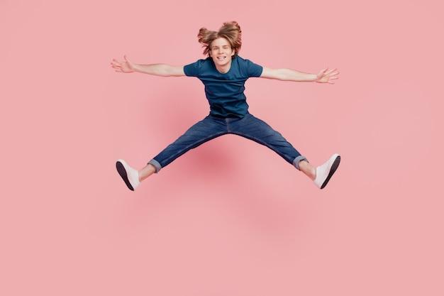 Portrait de beau funky beau mec sauter profiter du temps libre de vacances sur fond rose