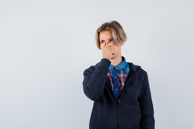 Portrait d'un beau garçon adolescent pinçant le nez, sentant quelque chose de dégoûtant en chemise, sweat à capuche et ayant l'air mécontent de la vue de face
