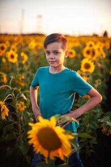 Portrait de beau garçon blond enfant sur champ de tournesol d'été