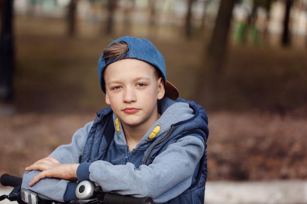 Portrait beau garçon sur un vélo à la route goudronnée dans le parc du printemps.