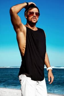 Portrait de beau hipster bronzé mannequin homme portant des vêtements décontractés en t-shirt noir et lunettes de soleil posant