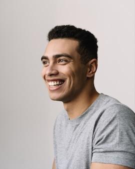 Portrait de beau homme afro-américain souriant portant un t-shirt gris décontracté, fond isolé