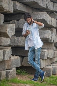 Portrait d'un beau jeune bavarder sur téléphone mobile en plein air