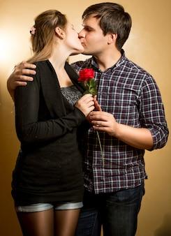 Portrait de beau jeune couple amoureux s'embrasser au studio