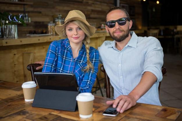 Portrait de beau jeune couple assis à table dans un café