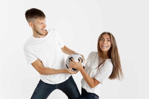 Portrait de beau jeune couple fans de football ou de football sur studio blanc