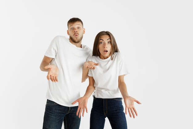 Portrait de beau jeune couple isolé sur fond de studio blanc. expression faciale, émotions humaines, concept publicitaire. copyspace. la femme et l'homme ont l'air choqués, étonnés et émerveillés.