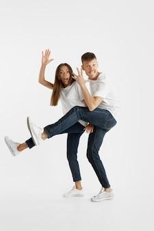 Portrait de beau jeune couple isolé sur mur blanc. expression faciale, émotions humaines, concept publicitaire. copyspace. femme et homme sautant, dansant ou courant ensemble.