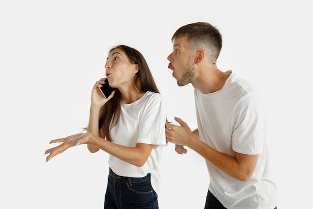 Portrait de beau jeune couple isolé sur mur blanc. expression faciale, émotions humaines, concept publicitaire. femme parlant au téléphone, l'homme veut porter son attention sur lui-même.