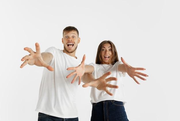 Portrait de beau jeune couple isolé sur mur blanc studio