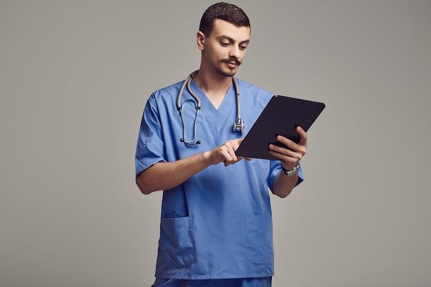 Portrait de beau jeune docteur arabe confiant avec moustache fantaisie en bleu tient la tablette