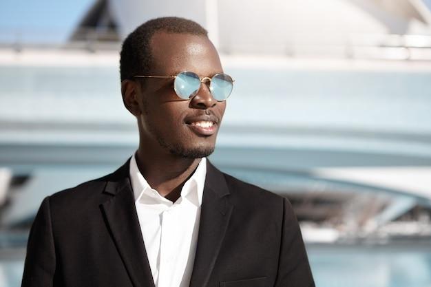 Portrait de beau jeune entrepreneur à succès posant à l'extérieur dans un environnement urbain