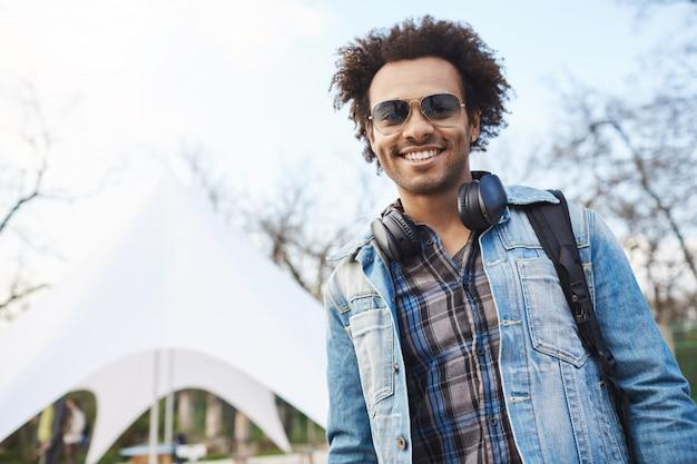Portrait de beau jeune étudiant afro-américain avec une coiffure afro souriant