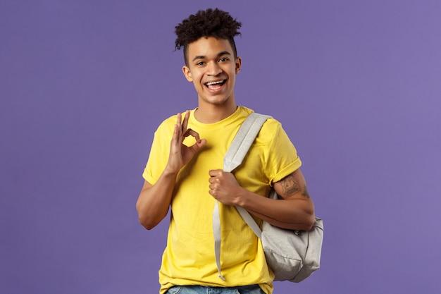 Portrait de beau jeune étudiant masculin montrant le geste.