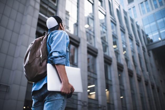 Portrait de beau jeune étudiant avec sac à dos debout à fond de bâtiment dans la rue