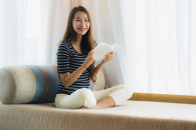 Portrait, beau, jeune femme asiatique, lecture, livre, sur, sofa, dans, salon
