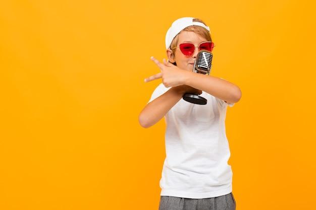 Portrait de beau jeune garçon de race blanche en t-shirt blanc et pantalon gris sourit et chante des chansons