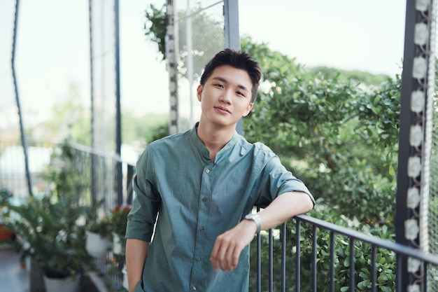 Un portrait d'un beau jeune homme adulte qui s'appuie sur une balustrade, avec le soleil qui brille et les arbres autour.
