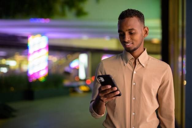 Portrait de beau jeune homme d'affaires africain noir portant des vêtements décontractés à l'extérieur en ville et à l'aide de téléphone mobile