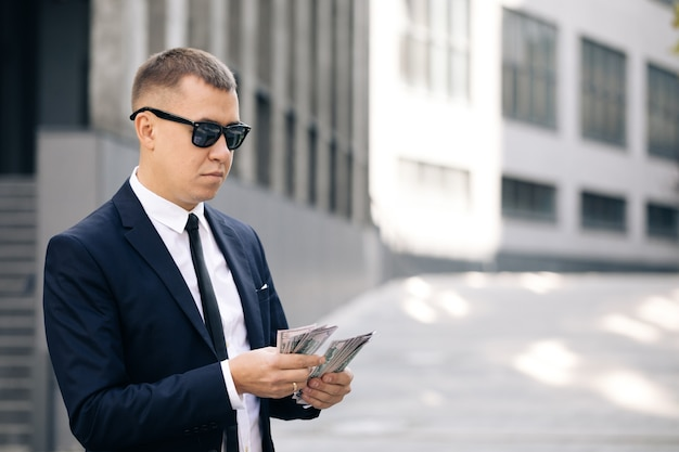 Portrait de beau jeune homme d'affaires caucasien à lunettes de soleil comptant de l'argent tout en se tenant à l'extérieur
