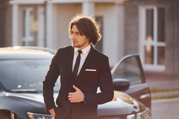 Portrait de beau jeune homme d'affaires en costume noir et cravate à l'extérieur près d'une voiture moderne dans la ville.