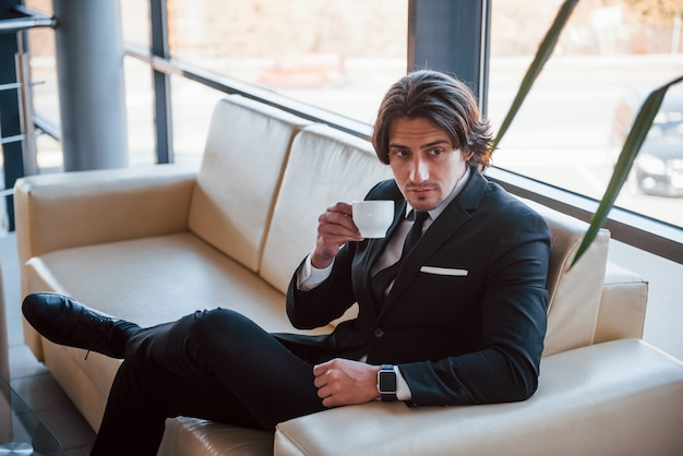 Portrait de beau jeune homme d'affaires en costume noir et cravate qui est assis sur le canapé et fait une pause.