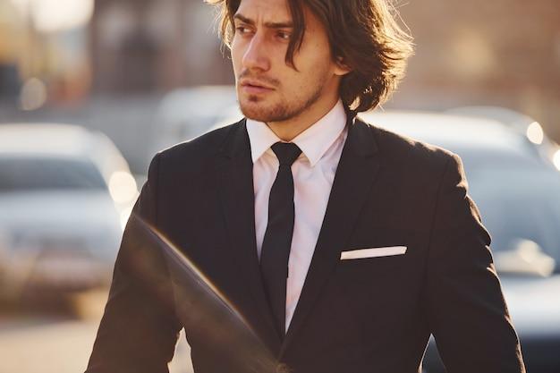Portrait de beau jeune homme d'affaires en costume noir et cravate se dresse dans la ville aux beaux jours.