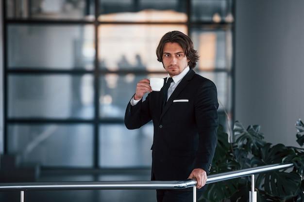 Portrait de beau jeune homme d'affaires en costume noir et cravate se tient à l'intérieur avec une tasse de boisson.