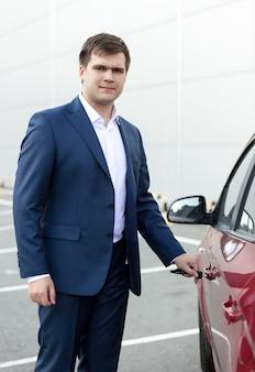 Portrait de beau jeune homme d'affaires ouvrant la porte de la voiture