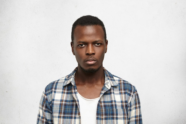 Portrait de beau jeune homme afro-américain avec une expression sérieuse et confiante sur son visage