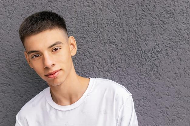 Portrait d'un beau jeune homme d'âge adolescent debout près d'un mur de béton, mode de vie, tendances de la jeunesse, thème lgbtq, fierté