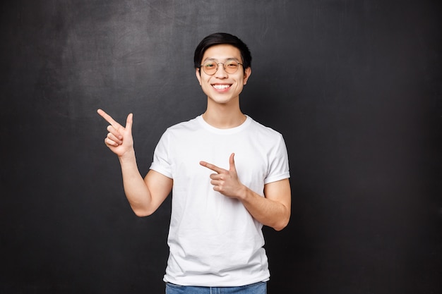 Portrait de beau jeune homme asiatique, étudiant en chemise blanche, pointant les doigts dans le coin supérieur gauche de la promo, offre de rabais ou bannière, caméra souriante, suggère un lien de visite,