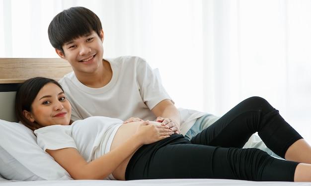 Portrait d'un beau jeune homme asiatique et d'une femme allongée sur un lit ensemble. ils sourient joyeusement et touchent le ventre d'une mère enceinte.