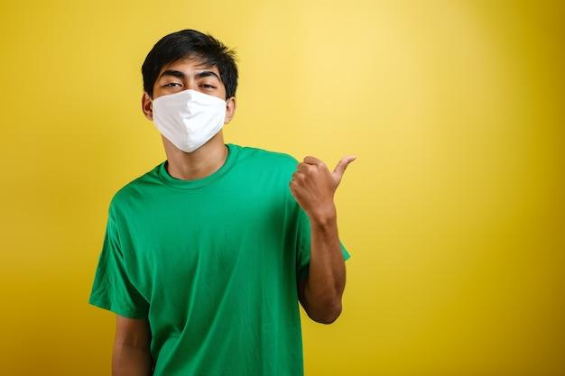Portrait d'un beau jeune homme asiatique portant un masque de protection médicale pointant son doigt sur l'espace de copie latéral. concept de lutte contre le coronavirus covid-19, sur fond jaune