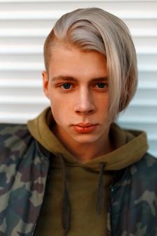 Portrait d'un beau jeune homme aux cheveux dans une veste militaire avec une capuche