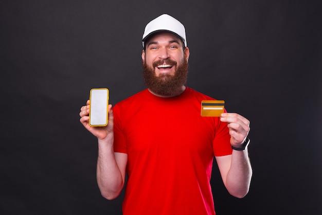 Portrait de beau jeune homme avec barbe montrant smartphone et carte de crédit