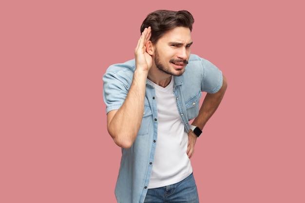 Portrait d'un beau jeune homme barbu attentif en chemise bleue de style décontracté, debout avec la main sur l'oreille et essayant d'entendre quelque chose avec un visage sérieux. tourné en studio intérieur, isolé sur fond rose.