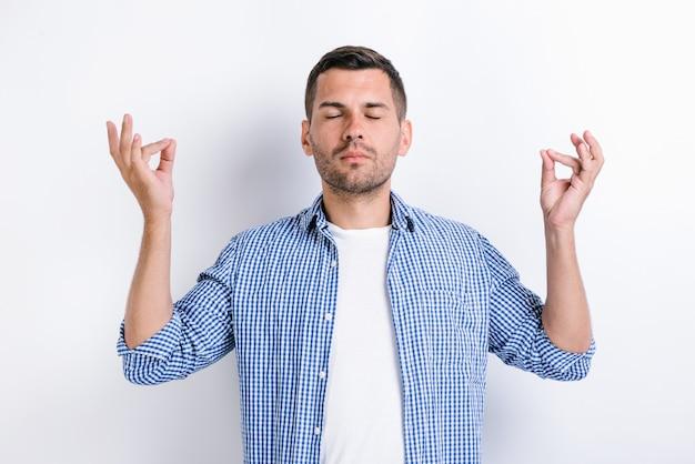 Portrait d'un beau jeune homme barbu calme et détendu debout avec les bras levés et faisant du yoga exercice de méditation. prise de vue en studio intérieur, isolé sur fond blanc