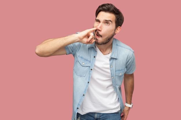Portrait d'un beau jeune homme barbu fou en chemise bleue de style décontracté debout et perçant son nez avec une grimace. tourné en studio intérieur, isolé sur fond rose.