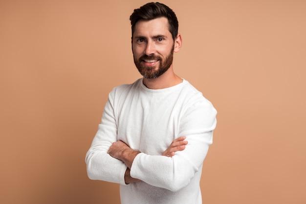 Portrait de beau jeune homme barbu heureux debout avec les bras croisés et regardant la caméra avec un sourire à pleines dents. studio intérieur tourné isolé sur fond beige