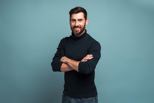 Portrait d'un beau jeune homme barbu heureux et réussi, debout avec les bras croisés et regardant la caméra avec le sourire. studio intérieur tourné, isolé sur fond bleu