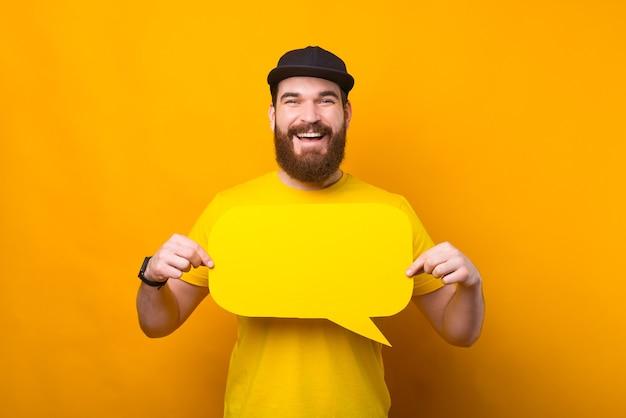 Portrait de beau jeune homme barbu joyeux tenant bulle jaune vide
