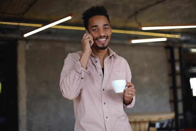 Portrait de beau jeune homme barbu à la peau foncée à la joyeusement avec un large sourire charmant, boire du thé et faire appel avec son téléphone portable, habillé en chemise beige