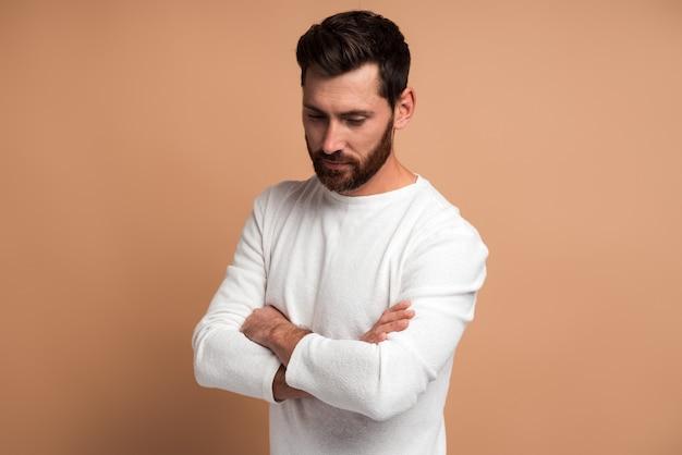 Portrait de beau jeune homme barbu pensif debout avec les bras croisés et regardant vers le bas avec une expression méditante tout en posant devant la caméra sur fond beige